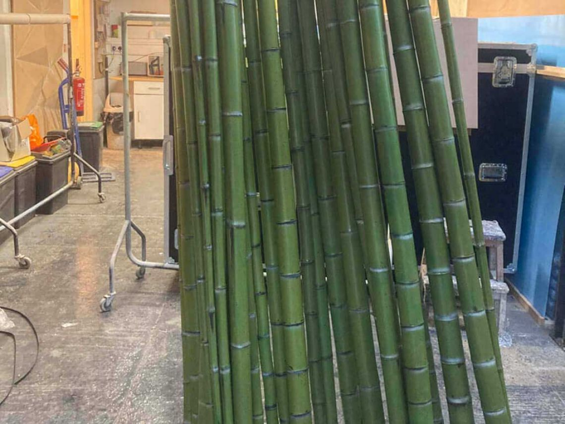 Lots of bamboo props stood up after being varnished.