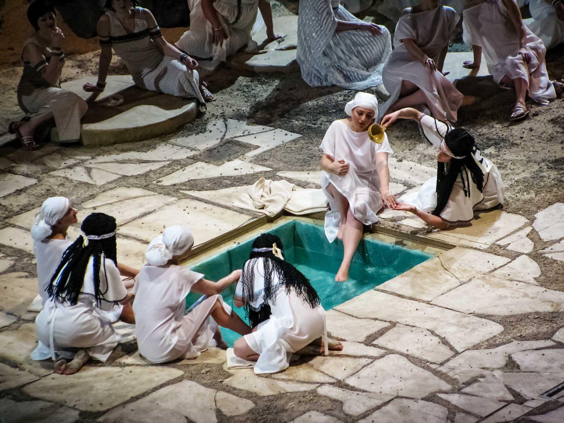 Close up of people performing at aida opera looking at giant spa prop.