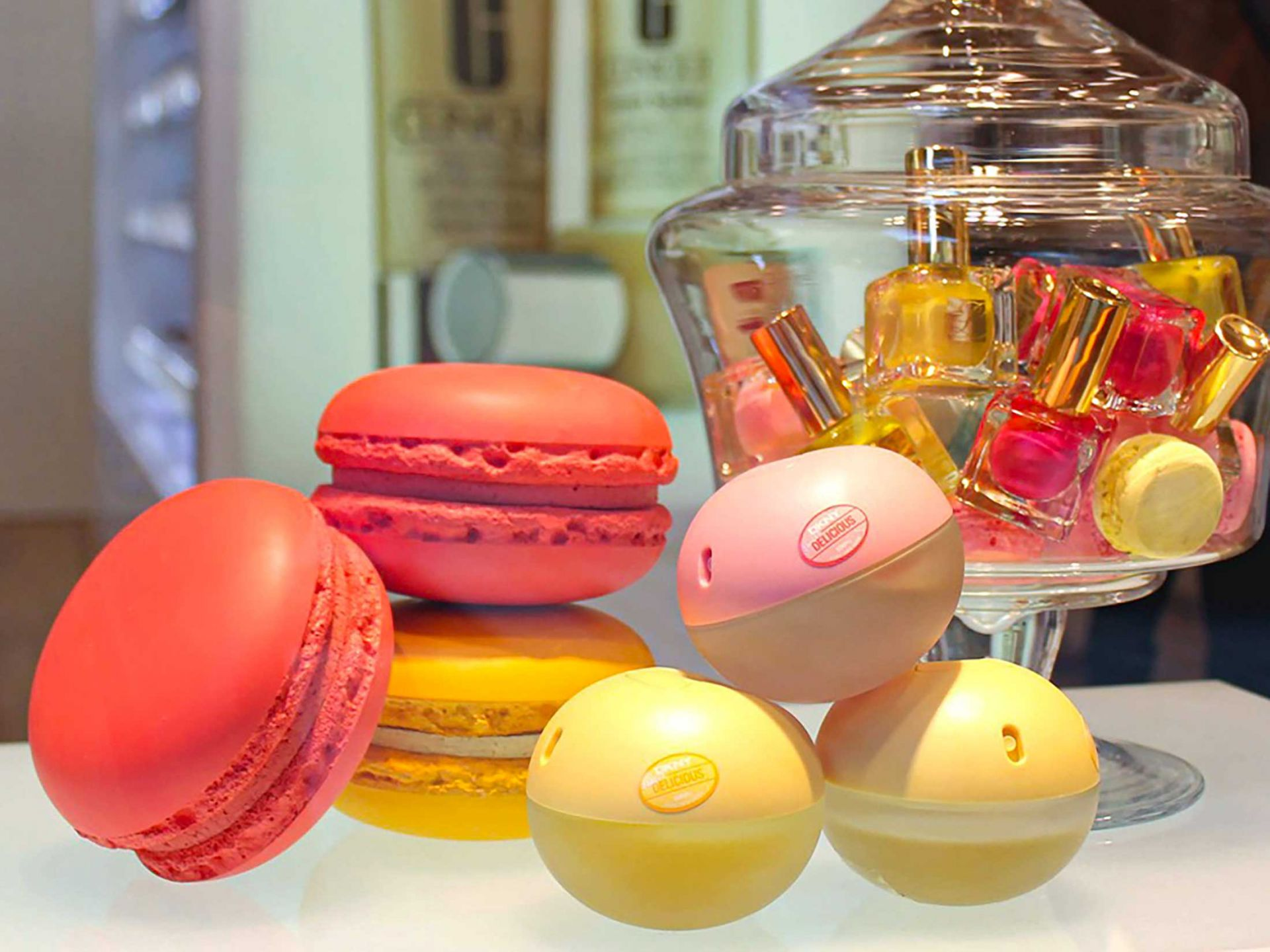 Macaron props in a promotional display with perfume and nail varnish.