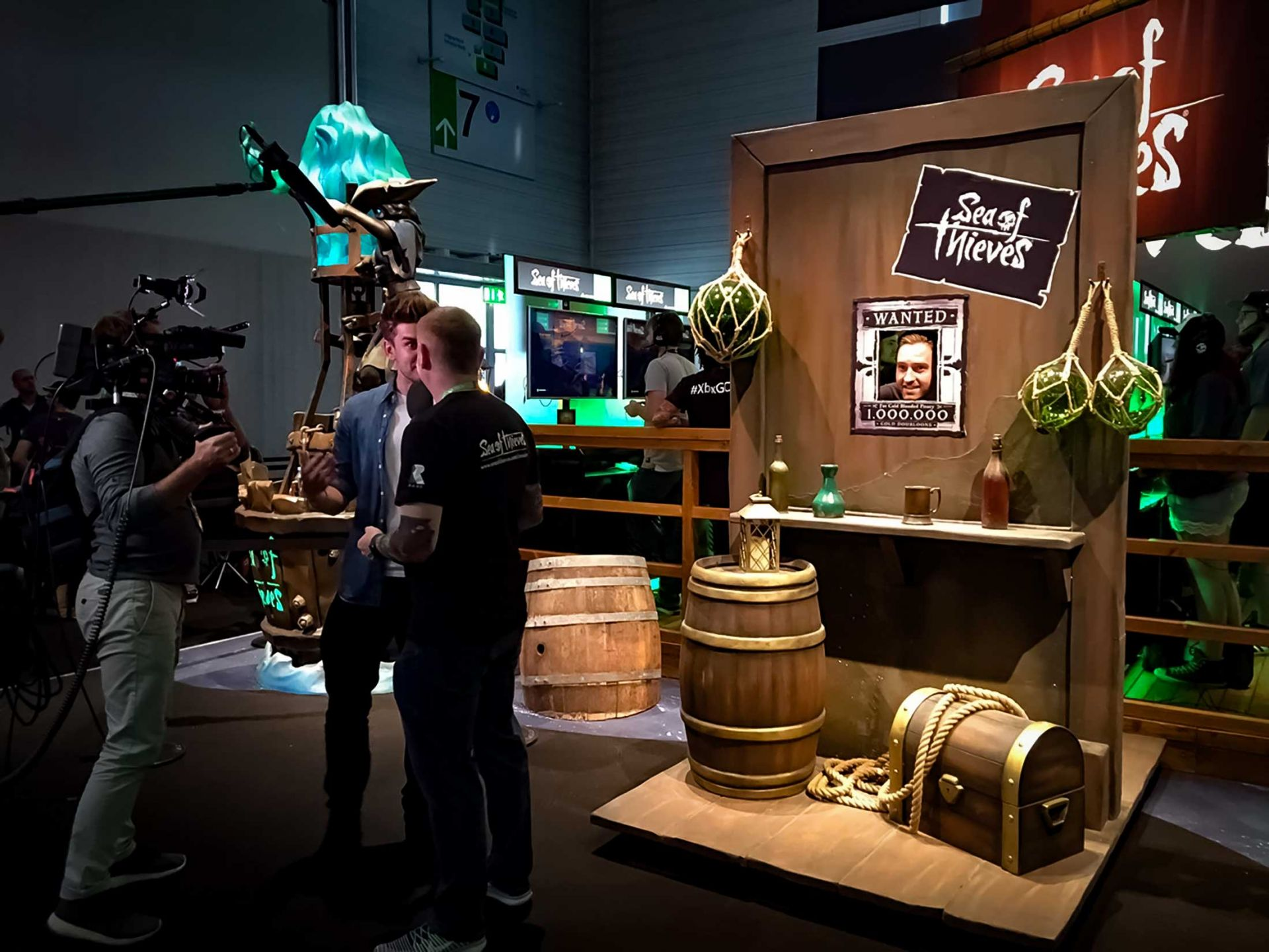 Sea of thieves expo with a man being interviewed in front of a camera and a wall and barrel prop.
