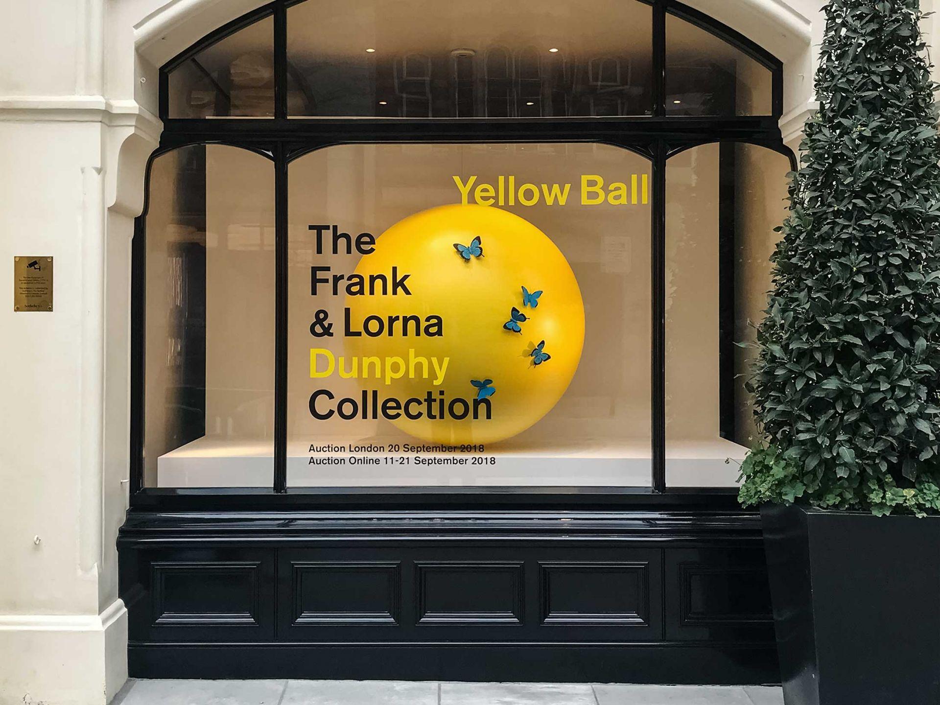 Giant yellow ball prop in window display.