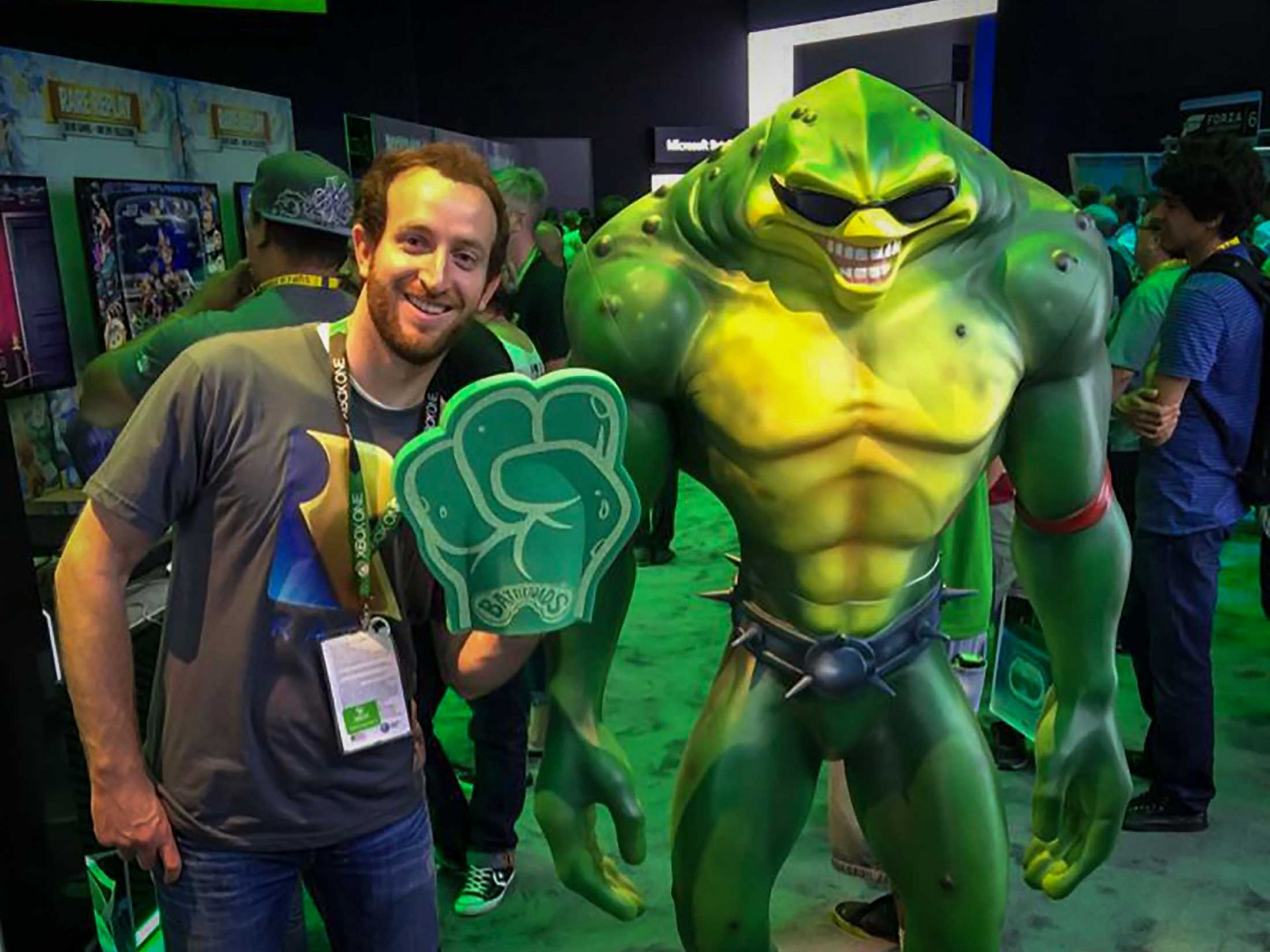 Man having his photo taken with battletoad giant sculpture.