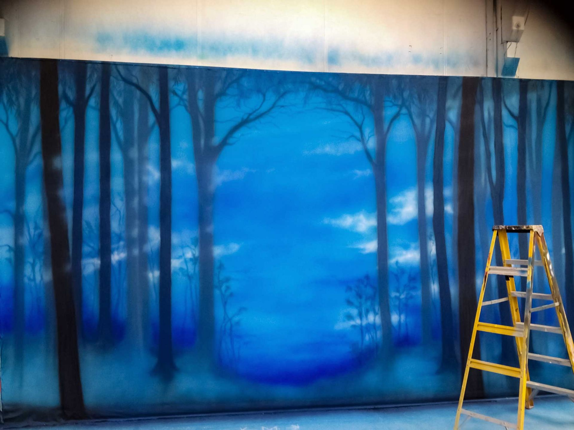 Blue scenic painting with dark trees fading into the background.