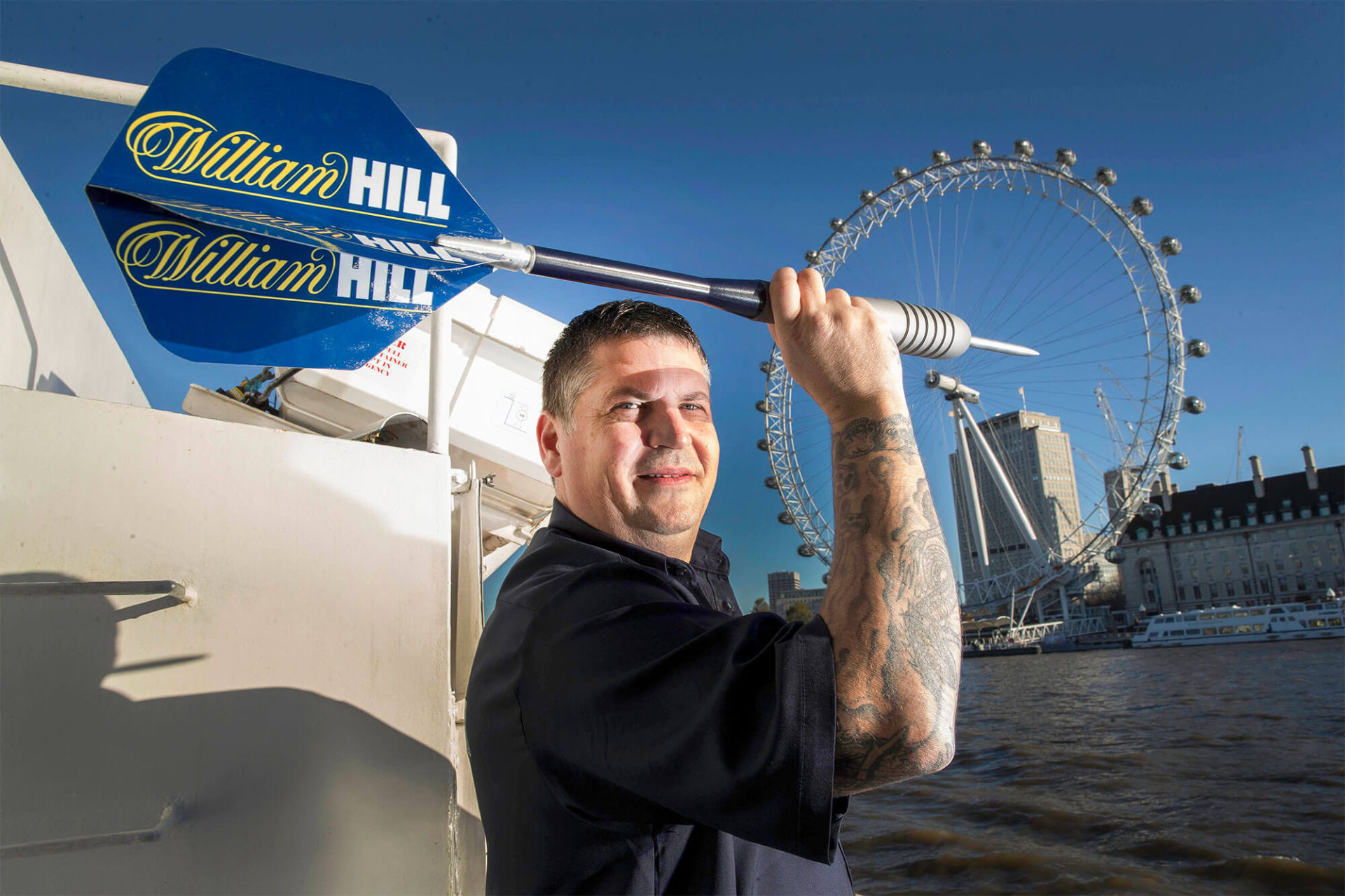 A man holding a giant dart prop with william hill logo.