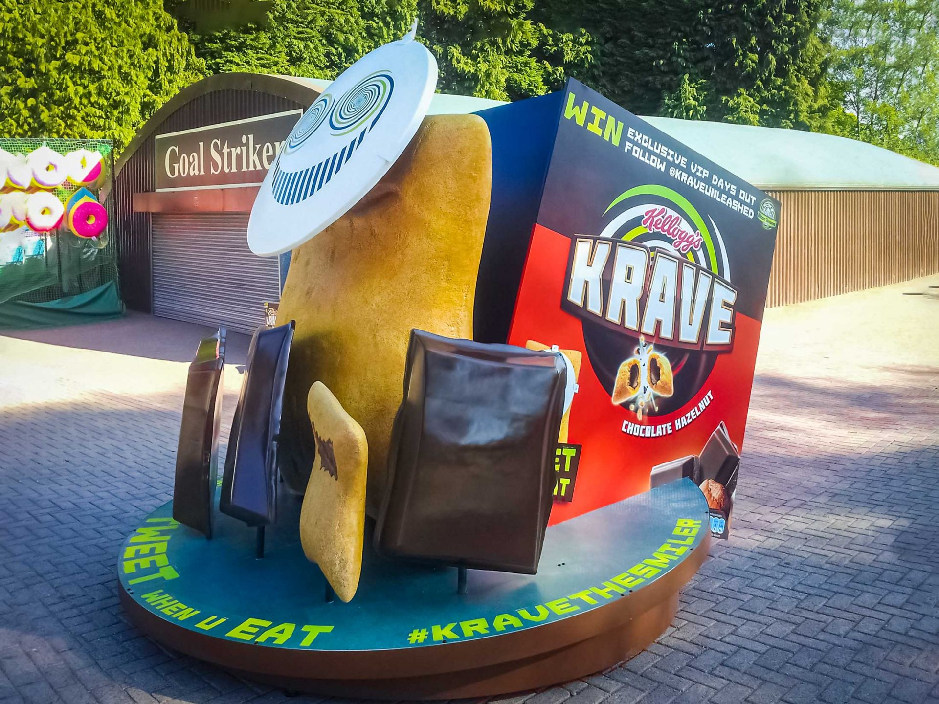 Giant cereal box prop with giant chocolate pieces on it's side at theme park.